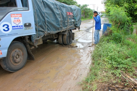 MUANG, MAHASARAKHAM - SEPTEMBER 7 : Truck wheels are fallen into hole and unidentified men are digging road hole on September 7, 2012 at local road, Muang, Mahasarakham, Thailand.
