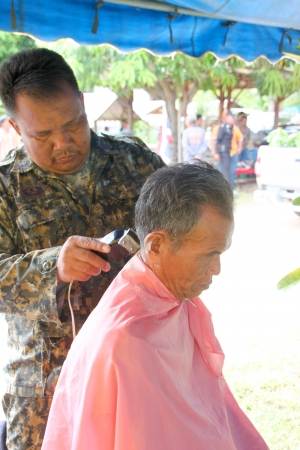 prettify: MUANG, MAHASARAKHAM - SEPTEMBER 19 : The unidentified barber is cutting an old man hair in public secter services mobile project on September 19, 2012 at Wat Don Whan, Muang, Mahasarakham, Thailand. Editorial