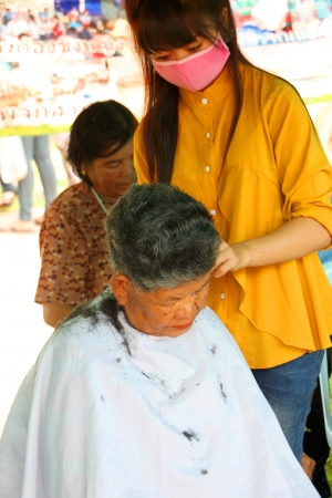 MUANG, MAHASARAKHAM - SEPTEMBER 19 : The unidentified barber is cutting an old woman hair in public secter services mobile project on September 19, 2012 at Wat Don Whan, Muang, Mahasarakham, Thailand. Stock Photo - 15453143