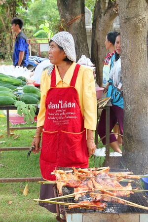 country store: MUANG, MAHASARAKHAM - SEPTEMBER 19 : Unidentified woman is selling grilled chicken in public secter services mobile project on September 19, 2012 at Wat Don Whan, Muang, Mahasarakham, Thailand.