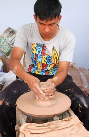 MUANG, BURIRAM - SEPTEMBER 9 : Unidentified man is showing group of tourists how to mold earthenware pots on September 9, 2012 at Taveekit Plaza, Muang, Buriram, Thailand.
