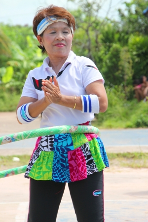 MUANG, MAHASARAKHAM - OCTOBER 5 : Unidentified old woman is performing hoola hoop with Thai dance in healthy way of life festival on October 5, 2012 at sport ground, Kerng local administration institute, Muang, Mahasarakham, Thailand.