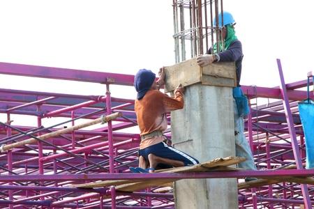coolie hat: MUANG, BURIRAM - SEPTEMBER 23 : Unidentified men are working in the building site on September 23, 2012 at Taweekit Plaza, Muang, Buriram, Thailand.