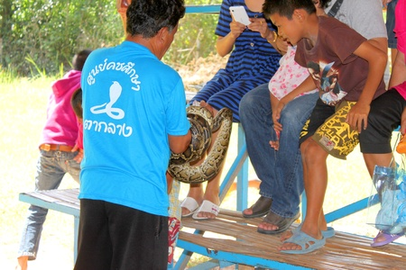 THA TUM, SURIN, THAILAND - OCTOBER 28 : Unidentified man is performing in snake show on October 28, 2012 at elephant study center, Ban Ta Klang, Tha Tum, Surin, Thailand.