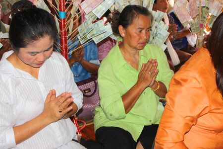 priest's ritual robes: MUANG, MAHASARAKHAM - NOVEMBER 9 : Unidentified Buddhists are making religious ceremony  in which yellow robes and money are presented to the priests at the end of Buddhist Lent on November 9, 2012 at Nong Whai temple, Tha Tum District, Muang, Mahasarakha Editorial