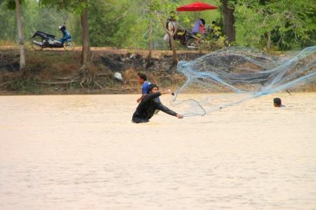 NACHUAK, MAHASARAKHAM - MARCH 31 : Unidentified men are catching freshwater fishes on March 31, 2012 at local reservoir, Nachuak, Mahasarakham, Thailand. Stock Photo - 16743534
