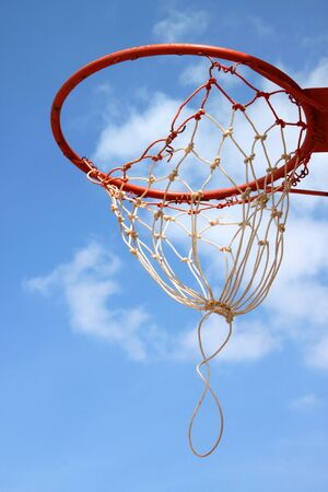 the height of a rim: Basketball net against blue sky background