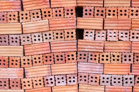 ordelijk: Ordelijke stapel van de bouw rode gebakken klei bakstenen