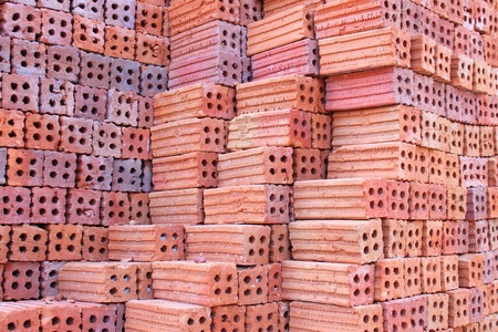 Orderly pile of construction red baked clay bricks photo