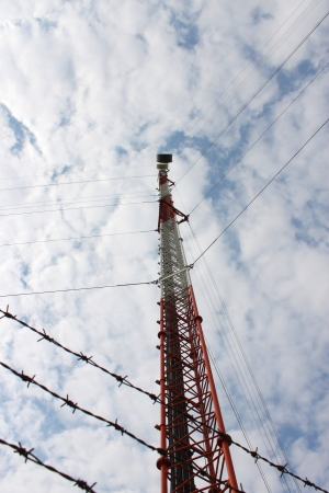 Telecommunication tower and antenna against blue sky photo