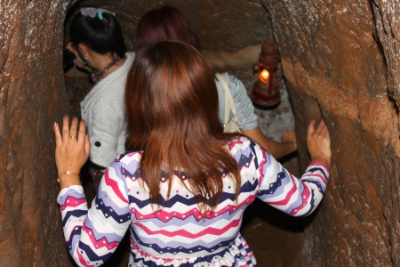 VINH MOC, QUANG TRI, VIETNAM - DECEMBER 10 : Unidentified tourists are walking into underground tunnel used during B52 carpet bombing between Vietnam war on December 10, 2012 at Vinh Moc, Quang Tri, Vietnam.
