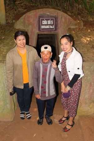 VINH MOC, QUANG TRI, VIETNAM - DECEMBER 10 : Unidentified tourists are taking photograph with one of men who ever live into underground tunnel used during B52 carpet bombing between Vietnam war on December 10, 2012 at Vinh Moc, Quang Tri, Vietnam.