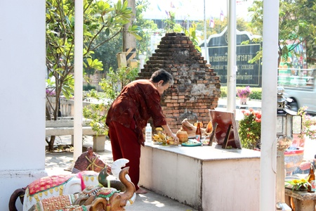 glorify: MUANG, MAHASARAKHAM - DECEMBER 12 : Unidentified woman is preparing fresh fruits, pork and chicken  for worshipping the shrine of city pillar on DECEMBER 12, 2012 at The shrine of city pillar, Muang, Mahasarakham, Thailand.