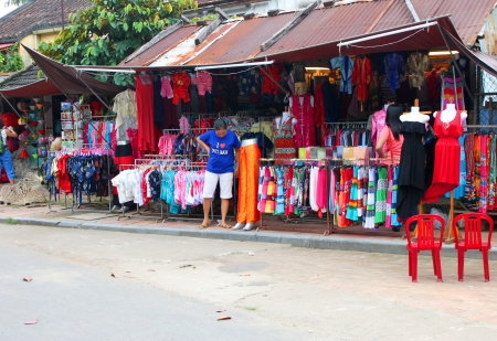 HOI AN, CENTRAL VIETNAM - DECEMBER 8 : Unidentified woman is buying goods and souvenirs on December 8, 2012 at Hoi An, Vietnam. So wonderful with old aged traditionally kept cultural activities, habits and customs, Hoai An town is now a wonderful living u Stock Photo - 16919774