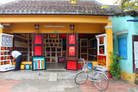 communual: HOI AN, CENTRAL VIETNAM - DECEMBER 8 : Unidentified man is buying goods and souvenirs on December 8, 2012 at Hoi An, Vietnam. So wonderful with old aged traditionally kept cultural activities, habits and customs, Hoai An town is now a wonderful living urb Editorial