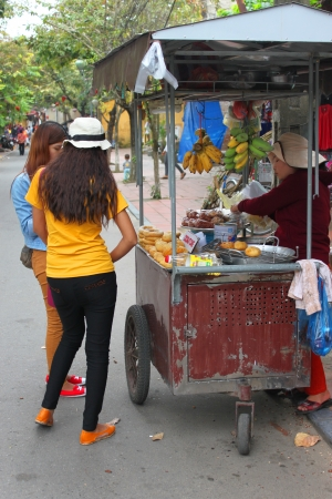 communual: HOI AN, CENTRAL VIETNAM - DECEMBER 8 : Unidentified tourists are buying food on December 8, 2012 at walking street in Hoi An, Vietnam. So wonderful with old aged traditionally kept cultural activities, habits and customs, Hoai An town is now a wonderful l