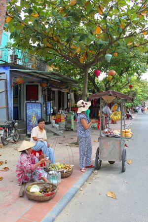 communual: HOI AN, CENTRAL VIETNAM - DECEMBER 8 : Unidentified women are selling food on December 8, 2012 at walking street in Hoi An, Vietnam. So wonderful with old aged traditionally kept cultural activities, habits and customs, Hoai An town is now a wonderful liv Editorial