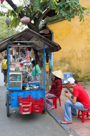 HOI AN, CENTRAL VIETNAM - DECEMBER 8 : Unidentified man is drinking beverage on December 8, 2012 at walking street in Hoi An, Vietnam. So wonderful with old aged traditionally kept cultural activities, habits and customs, Hoai An town is now a wonderful l Stock Photo - 16919784