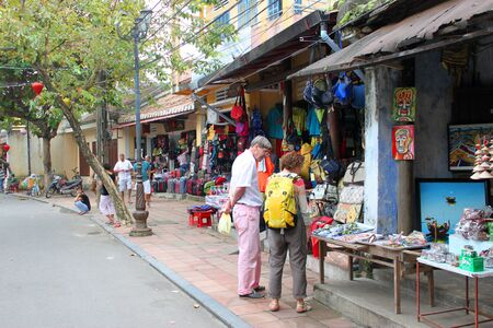 communual: HOI AN, CENTRAL VIETNAM - DECEMBER 8 : Unidentified tourists are buying goods and souvenirs on December 8, 2012 at walking street and cycling in Hoi An, Vietnam. So wonderful with old aged traditionally kept cultural activities, habits and customs, Hoai A