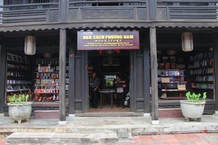 communual: HOI AN, CENTRAL VIETNAM - DECEMBER 8 : Unidentified tourists are buying books, goods and souvenirs on December 8, 2012 at bookstore in Hoi An, Vietnam. So wonderful with old aged traditionally kept cultural activities, habits and customs, Hoai An town is