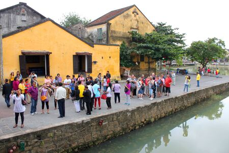 communual: HOI AN, CENTRAL VIETNAM - DECEMBER 8 : Unidentified tourists are traveling to old house and Japanese covered bridge on the bank of Hoai River on December 8, 2012 at Hoi An, Vietnam. So wonderful with old aged traditionally kept cultural activities, habits