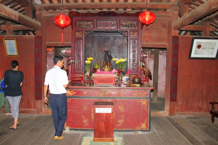 communual: HOI AN, CENTRAL VIETNAM - DECEMBER 8 : Unidentified tourists are worshipping the shrine on Japanese covered bridge on December 8, 2012 at Hoi An, Vietnam. So wonderful with old aged traditionally kept cultural activities, habits and customs, Hoai An town  Editorial
