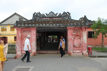 communual: HOI AN, CENTRAL VIETNAM - DECEMBER 8 : Unidentified tourists are traveling to Japanese covered bridge on the bank of Hoai River on December 8, 2012 at Hoi An, Vietnam. So wonderful with old aged traditionally kept cultural activities, habits and customs,