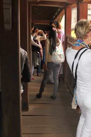 HOI AN, CENTRAL VIETNAM - DECEMBER 8 : Unidentified tourists are traveling to Japanese covered bridge on the bank of Hoai River on December 8, 2012 at Hoi An, Vietnam. So wonderful with old aged traditionally kept cultural activities, habits and customs,