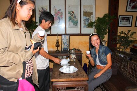 Tea services in old house of Duc An on walking street and cycling of world heritage old town on December 8, 2012 at Hoi An, Vietnam. So wonderful with old aged traditionally kept cultural activities, habits and customs, Hoai An town is now a wonderful liv Stock Photo - 16943465
