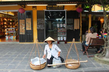 HOI AN, CENTRAL VIETNAM - DECEMBER 8 : Unidentified woman is selling food on footpath of walking street and cycling of world heritage old town on December 8, 2012 at Hoi An, Vietnam. So wonderful with old aged traditionally kept cultural activities, habit Stock Photo - 16972946