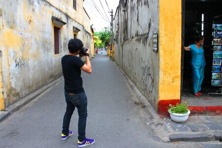 communual: HOI AN, CENTRAL VIETNAM - DECEMBER 8 : Unidentified tourist is taking photograph on walking street and cycling of world heritage old town on December 8, 2012 at Hoi An, Vietnam. So wonderful with old aged traditionally kept cultural activities, habits and