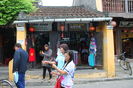 HOI AN, CENTRAL VIETNAM - DECEMBER 8 : Unidentified tourists are shopping on walking street and cycling of world heritage old town on December 8, 2012 at Hoi An, Vietnam. So wonderful with old aged traditionally kept cultural activities, habits and custom Stock Photo - 16972926