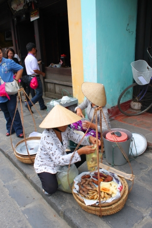 HOI AN, CENTRAL VIETNAM - DECEMBER 8 : Unidentified women are selling food on footpath of walking street and cycling of world heritage old town on December 8, 2012 at Hoi An, Vietnam. So wonderful with old aged traditionally kept cultural activities, habi Stock Photo - 16972933
