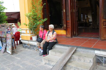 communual: HOI AN, CENTRAL VIETNAM - DECEMBER 8 : Unidentified tourists are relax sitting in front of one of old houses of world heritage old town on December 8, 2012 at Hoi An, Vietnam. So wonderful with old aged traditionally kept cultural activities, habits and c