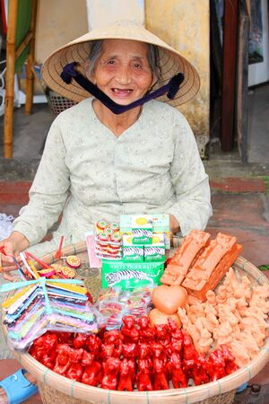 communual: HOI AN, CENTRAL VIETNAM - DECEMBER 8 : Unidentified woman is selling souvenirs on footpath of walking street and cycling of world heritage old town on December 8, 2012 at Hoi An, Vietnam. So wonderful with old aged traditionally kept cultural activities,