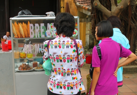 communual: HOI AN, CENTRAL VIETNAM - DECEMBER 8 : Unidentified tourists are buying food on footpath of walking street and cycling of world heritage old town on December 8, 2012 at Hoi An, Vietnam. So wonderful with old aged traditionally kept cultural activities, ha