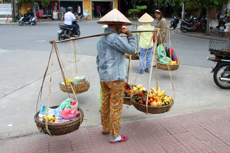 communual: HOI AN, CENTRAL VIETNAM - DECEMBER 8 : Unidentified women are selling fruits on footpath of walking street and cycling of world heritage old town on December 8, 2012 at Hoi An, Vietnam. So wonderful with old aged traditionally kept cultural activities, ha