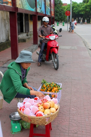 communual: HOI AN, CENTRAL VIETNAM - DECEMBER 8 : Unidentified woman is selling fruits on footpath of walking street and cycling of world heritage old town on December 8, 2012 at Hoi An, Vietnam. So wonderful with old aged traditionally kept cultural activities, hab Editorial