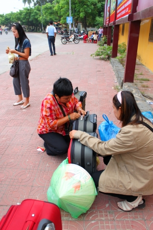 communual: HOI AN, CENTRAL VIETNAM - DECEMBER 8 : Unidentified tourists are packing suitcases on footpath of walking street and cycling of world heritage old town on December 8, 2012 at Hoi An, Vietnam. So wonderful with old aged traditionally kept cultural activiti