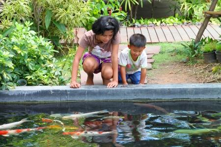 MUANG, BURIRAM - APRIL 8 : Unidentified children are looking at fishes in local aquarium garden park on April 8, 2012 at Muang, Buriram, Thailand. Stock Photo - 17063362