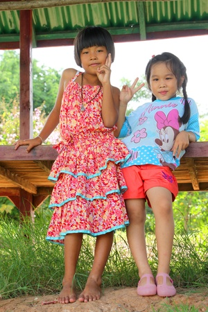 MUANG, MAHASARAKHAM - SEPTEMBER 22 : Unidentified girls are sending victory sign to tourists on September 22, 2012 at local village of Don Whan, Muang, Mahasarakham, Thailand. Stock Photo - 17063353