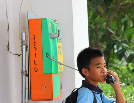 MUANG, MAHASARAKHAM - JUNE 8 : Unidentified boy is calling to somebody by telephone on June 8, 2012 at city hall of Muang, Mahasarakham, Thailand.