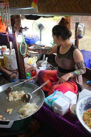 AYUTTHAYA, THAILAND - JANUARY 6 : Unidentified woman is selling food in Ayothaya Floating Market on January 6, 2013 at Ayutthaya, Thailand. Stock Photo - 17262755