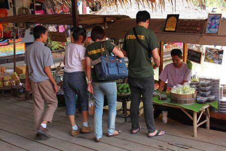 ayothaya: AYUTTHAYA, THAILAND - JANUARY 6 : Unidentified tourists are buying food in Ayothaya Floating Market on January 6, 2013 at Ayutthaya, Thailand.