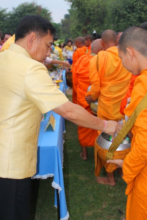 MUANG, MAHASARAKHAM - DECEMBER 5 : Mr.Noppawat Singhsakda, provincial governor and people are making religious merit, giving food offerings to Buddhist monks and celebrating the king Rama IX birthday on December 5, 2012 at city hall ground, Muang, Mahasar Stock Photo - 17712778