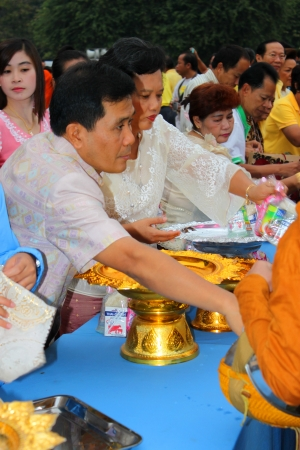 MUANG, MAHASARAKHAM - DECEMBER 5 : Unidentified people are making religious merit, giving food offerings to Buddhist monks and celebrating the king Rama IX birthday on December 5, 2012 at city hall ground, Muang, Mahasarakham, Thailand.