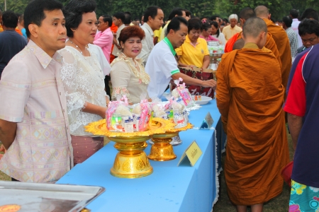 MUANG, MAHASARAKHAM - DECEMBER 5 : Unidentified people are making religious merit, giving food offerings to Buddhist monks and celebrating the king Rama IX birthday on December 5, 2012 at city hall ground, Muang, Mahasarakham, Thailand. Stock Photo - 17712791