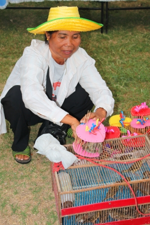 MUANG, MAHASARAKHAM - DECEMBER 5 : Unidentified woman is selling birds for someone to set them free or making religious merit and celebrating the king Rama IX birthday on December 5, 2012 at city hall ground, Muang, Mahasarakham, Thailand. Stock Photo - 17712809