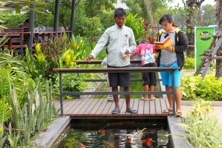 MUANG, BURIRAM - JANUARY 26 : Unidentified tourists are looking at fishes in local aquarium garden park on January 26, 2013 at Muang, Buriram, Thailand. Stock Photo - 17950148