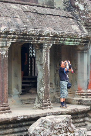handscraft: SIEMREAP, KHMER REPUBLIC - FEBRUARY 24 : Unidentified tourist is looking at stone carving of classical Khmer construction on February 24, 2013 at Angkor Wat, Siemreap, Khmer Republic. Editorial